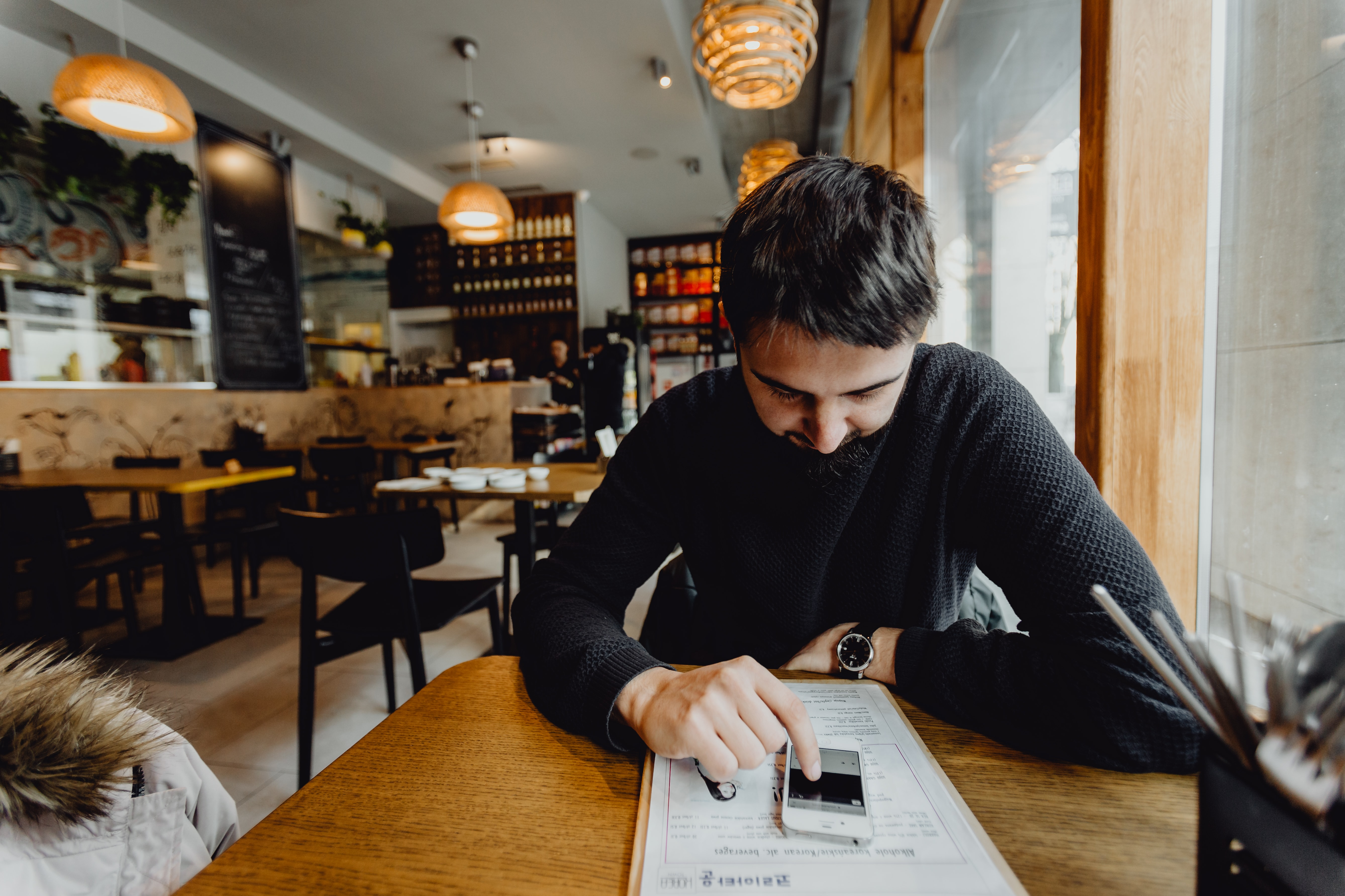 kaboompics_Man using his mobile phone in the restaurant